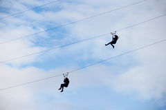 Silhouettes of two people coming down the cable tramway on a bac Stock Photo