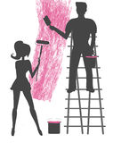 Silhouettes of two people painting a blank wall Royalty Free Stock Photography