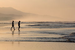 Silhouettes of two people walking on the beach. Silhouette of two people walking on the beach with morning light early in the morning in Matapalo, Costa Rica Stock Image