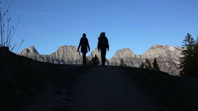 The silhouettes of two people walking down the mountain. The silhouettes of two people walking down the mountain on a background of blue sky stock video footage