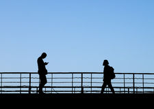 Silhouettes of two people walking towards each other by footbridge Stock Photography