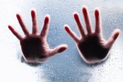 Silhouettes of two right hands. Behind wet glass Stock Photos
