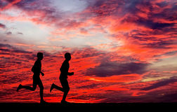 Silhouettes of two runners on fiery background. Silhouettes of two runners on sunset fiery background. Silhouettes of running mans against the colorful sky Stock Photography