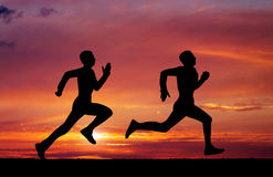 Silhouettes of two runners. On sunset fiery background Stock Image