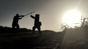 Silhouettes of two samurai fighting with swords in the rays of sunset.  Stock Photography