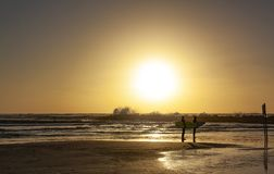 Silhouettes of two surfers at sunset on the beach royalty free stock photo