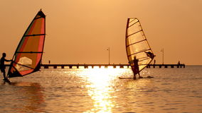 Silhouettes of two surfers at sunset. Man passing by with his windsurf while his friend stays on his surf or sailboard at sunset on a calm ocean against a stock video footage