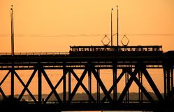 Silhouettes of a two-tiered bridge and 2 trams on a sunset background royalty free stock image