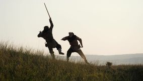 Silhouettes of two warriors Viking are fighting with swords. Contre-jour. Silhouettes of two Vikings are fighting with swords in the meadow. Medieval Reenactment stock video