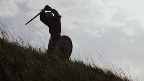 Silhouettes of two warriors Viking are fighting with swords and shields.