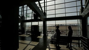 Silhouettes of two woman speaking in departure hall at airport. Woman worker with short haircut speaks, explains information about flight to passenger, gives stock video footage