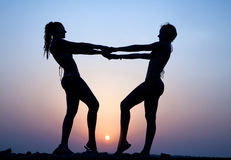 Silhouettes of two women. Silhouettes of two young women in swimming costumes  holding hands on the beach at sunset Stock Photo
