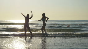Silhouettes of two women dancing on the shore of a beach stock video