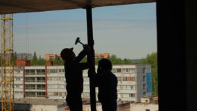 Silhouettes of two workers assemble a metal beam stock footage