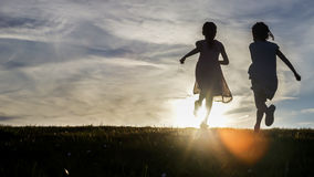 Silhouettes of two young children running towards the sunset Royalty Free Stock Image