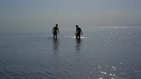 Two young men go knee-deep in the water. Silhouettes of two young men go knee-deep in the water of lake or sea stock video footage