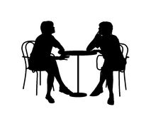 Two women sitting at the table. Silhouettes of two young women sitting at the table in a cafe and talking to each other Stock Illustration