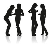 Silhouettes of two young women. Talking with each other royalty free stock photography