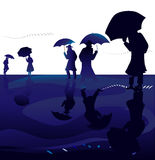 Silhouettes with umbrellas Stock Photography