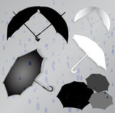 Silhouettes of umbrellas in the background of rain. Black and white umbrellas in the gray background Stock Image