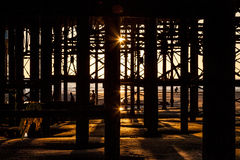Silhouettes under the pier. People in silhouette under the pier Stock Image