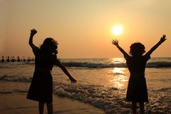 Children play at the beach during sunset royalty free stock photos