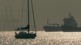 Silhouettes of an unknown anchored sailboat and big cargo ships near Gibraltar. Silhouettes of an anchored sailboat and cargo ships stock footage