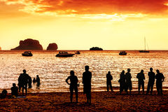 Silhouettes of unknown people watching red sunset Stock Images