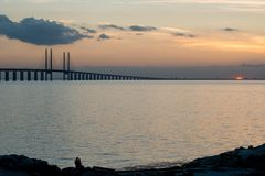 Oresund at dusk. Silhouettes of unrecognizable people at Limhamn in Malmo, Sweden enjoying the sunset at Oresund and Oresund Bridge Bridge Royalty Free Stock Photography