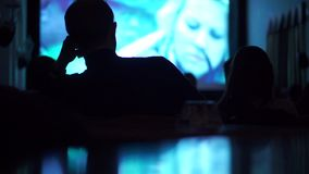 Silhouettes of unrecognizable people watching movie in dark cinema hall stock footage