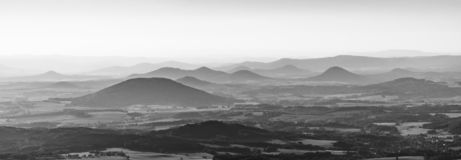 Silhouettes of volcanic hills of Ceske Stredohori, Central Bohemian Uplands, on sunny and hazy day. Czech Republic. Black and white image stock photo