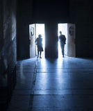 Silhouettes walking through doorway. Silhouette of male and female walking through separate doors Royalty Free Stock Photos