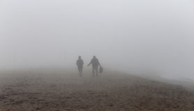Silhouettes walking under the fog in the beach Royalty Free Stock Photos