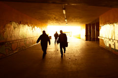 Silhouettes walking into an urban grunge tunnel Royalty Free Stock Photo
