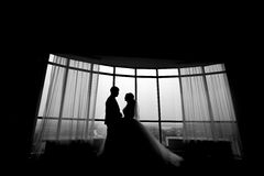 Silhouettes of wedding couple hugging at hotel room near window. Black and white Stock Photography