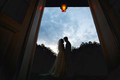 Silhouettes of a wedding couple standing in the front of deep bl Stock Photo