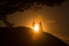 Silhouettes of wedding couple standing on hill. Royalty Free Stock Photography