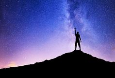 Silhouettes of winner on mountain peak. Sport and active life concept on the night sky background stock images