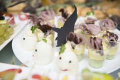 Silhouettes of witches among stuffed boiled eggs and octopus snacks in glasses stock photo