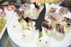 Silhouettes of witches among stuffed boiled eggs and octopus snacks in glasses stock images