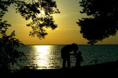 Silhouettes of woman and boy on sunset at the sea bay Stock Photo