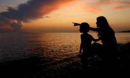 Silhouettes of the woman and child. Beside seaside on sundown Royalty Free Stock Photo