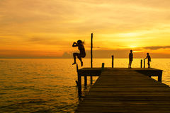 Silhouettes of woman jump into sea from pier Stock Photos