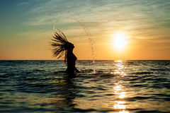 Silhouettes of woman jumping in ocean Stock Photo