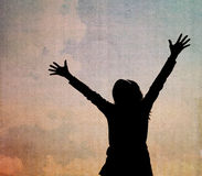 Silhouettes of woman with raised hands. Stock Photo
