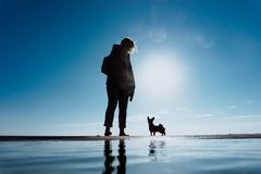 The silhouettes of a women and her dog at the beach with blue sky royalty free stock photography
