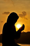 Silhouettes of a women praying Stock Photos