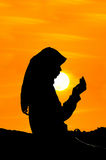 Silhouettes of a women praying Stock Photo