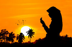 Silhouettes of a women praying. Silhouettes of a woman praying during sunset Royalty Free Stock Photos