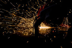 Silhouettes of Worker and sparks of bonfire while grinding iron. In dark room Stock Photo